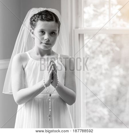 Young girl in white dress with a rosary