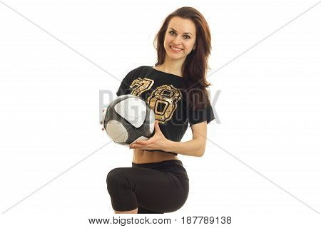 joyful young girl stands in sportswear holds the ball and laughs, isolated on white background