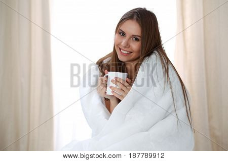 Woman wrapped in a blanket and holds a mug after wake up, entering a day happy and relaxed after good night sleep. Sweet dreams, good morning, new day, weekend, holidays concept.