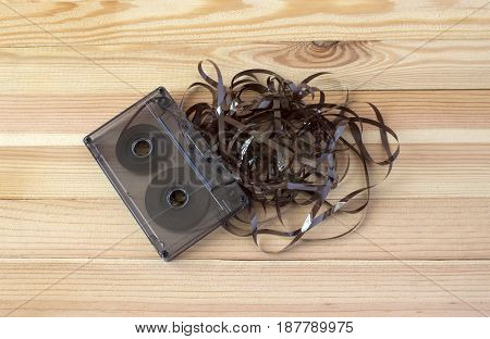 Transparent audio cassette with tangled film on a light wooden background