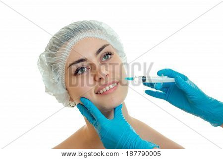 Portrait of a cheerful young girl in Hat smiling and that medical doctor makes it gloves prick at face close-up isolated on white background