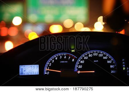 Close up car instrument panel with night light of the road.