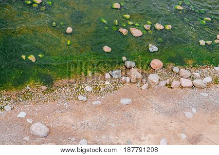 Top view of a beach with sand and stones in water and green emerald water with seaweed