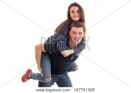 joyful young girl on shoulders by the beautiful fun guy isolated on white background