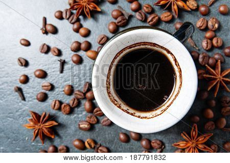 Coffee cup with coffee beans on stone table background with star anise. Top view