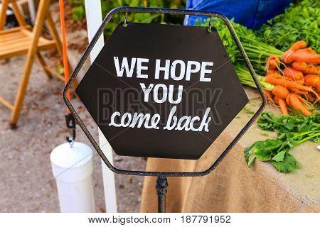 Punta Gorda, FL, USA - 01/16/2016: We Hope You Come Back sign seen at a farmers market in Punta Gorda FL