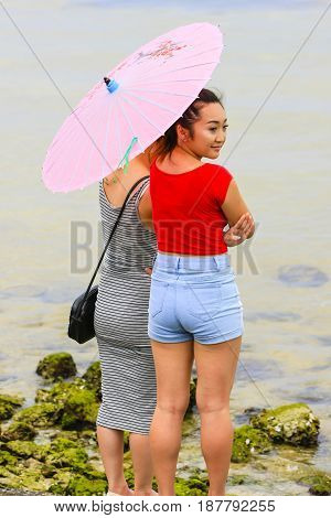Tampa Bay, FL, USA - 09/05/2016:Two asian girls standing at the waters edge of Tampa bay holding a paper parasol