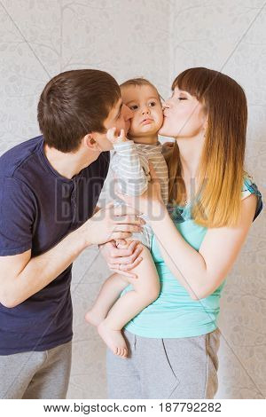 Young happy parents kissing baby boy, mother and father and son