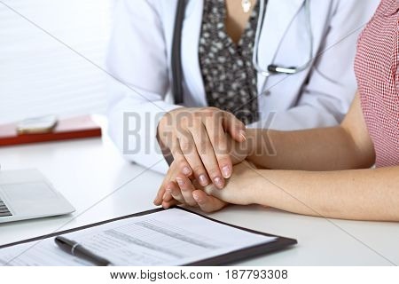 Close-up of doctor  reassuring her female patient. Medical ethics and trust concept.