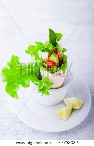 Vegetable wrap sandwiches with greenery on a white surface