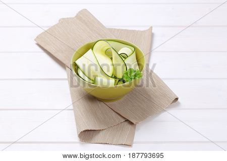 bowl of raw zucchini strips on beige place mat