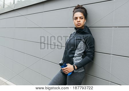 Young female runner leaning against wall, drinking water
