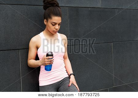 A woman during a workout taking a break outside