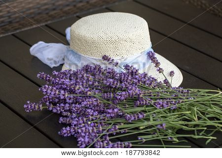 Lavender flowers and white hat on black table