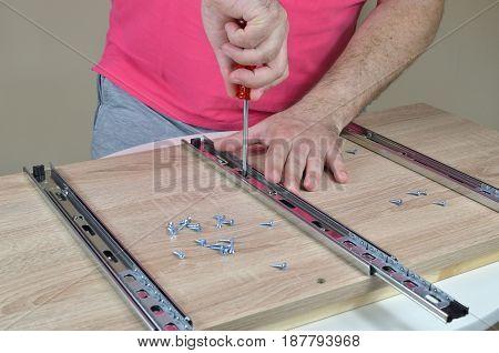 Man Assembling Elements Of A Furniture
