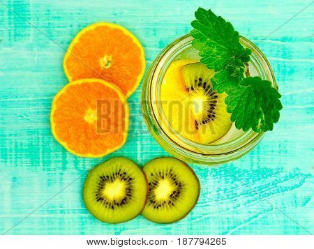 Citrus fruit and herbs water for detox or dieting in glass bottles on wooden board blue background selective focus square crop. Clean eating weight loss healthy lifestyle concept