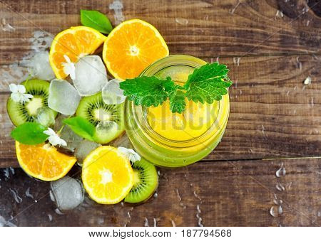 Citrus fruit and herbs water for detox or dieting in glass bottles on wooden board dark background selective focus square crop. Clean eating weight loss healthy lifestyle concept