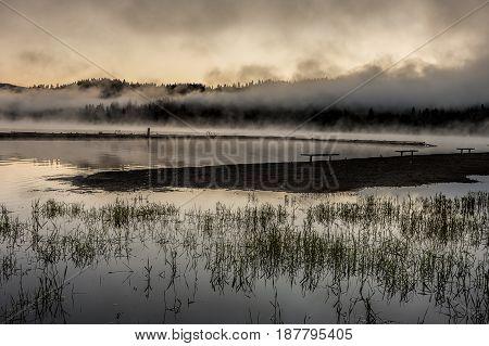 An orange sunrise over the calm Hauser Lake in Idaho.