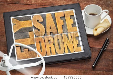fly safe drone  - word abstract in vintage letterpress wood type on a digital tablet with a drone propeller and coffee