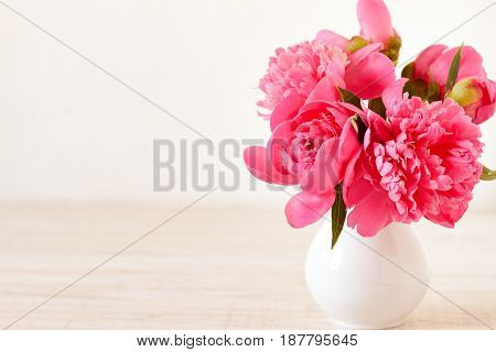 Pink peonies in vase on wood background