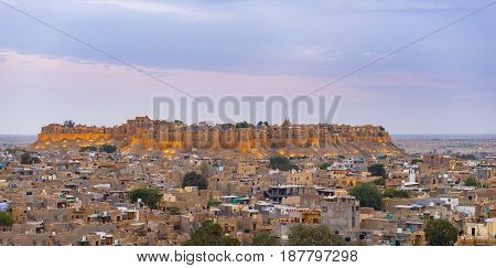 Jaisalmer cityscape at dusk. The majestic fort dominating the city. Scenic travel destination and famous tourist attraction in the Thar desert Rajasthan India.