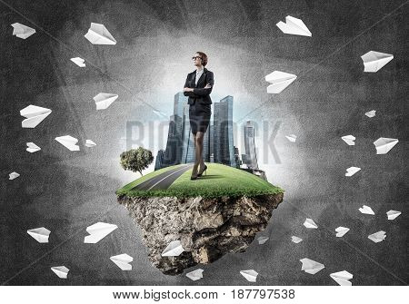 Elegant confident businesswoman standing on green floating island against concrete background