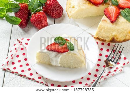 Cottage cheese casserole with coconut shavings. It is decorated with fresh strawberries and mint. Delicious and healthy breakfast. Served with yoghurt sauce and strawberries