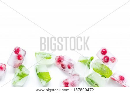 fresh cranberry frozen in ice cubes on white desk background top view mock-up