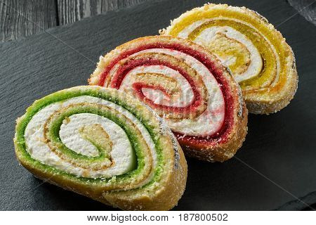 Delicious cake roll with fruit marmalade (kiwi strawberry lemon) and marshmallow. Sliced rolls on a slate plate. Tasty fruit dessert. Selective focus
