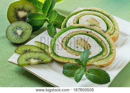 Delicious cake roll with kiwi marmalade and marshmallow. Sliced rolls on a plate fresh kiwi and mint. Tasty fruit dessert
