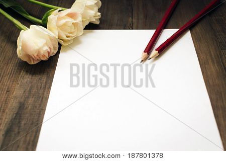 Blank sheet of white paper, red pencils and tulips on dark wooden desk. Business concept. Template