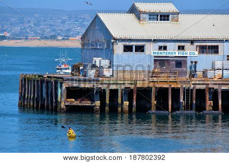 May 10, 2017 in Monterey, CA:  Person kayaking next to the Monterey Fish Company open daily where people can purchase fresh seafood taken in Monterey Bay, CA