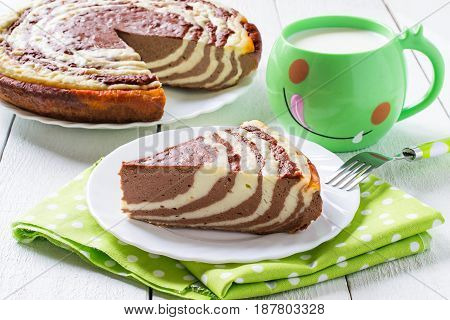 Delicious homemade chocolate cake with cottage cheese Zebra (Marble cake). The cake is cut into pieces served with milk. Tasty breakfast