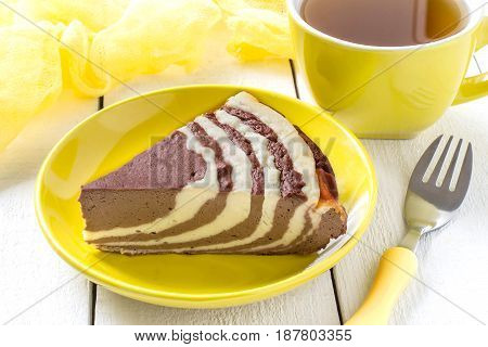 Delicious homemade chocolate cake with cottage cheese Zebra (Marble cake). Tasty breakfast. Piece is cut from cake yellow cup of tea and yellow gauze textiles on white wooden table. Selective focus