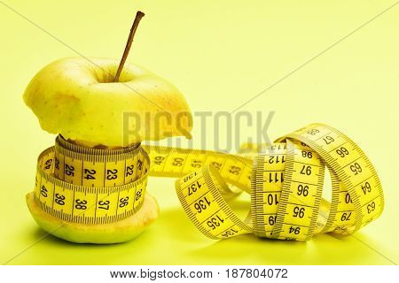Concept of low calorie food: bitten apple belted with tape measuring on yellow background