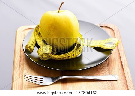 Weight loss and healthy diet concept represented by fresh yellow apple on black plate yellow measuring tape knotted around and metal fork on wooden cutting board grey background