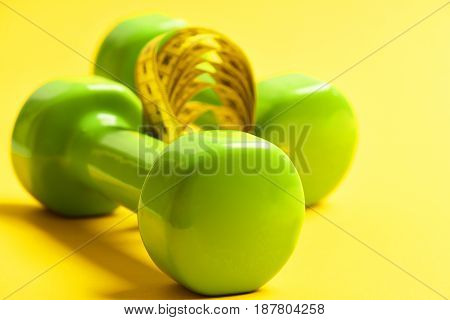 Dumbbells In Green Color With Measuring Tape On Yellow