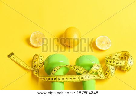Nutrition, Diet Concept. Measuring Tape Twined Around Dumbbells Isolated White