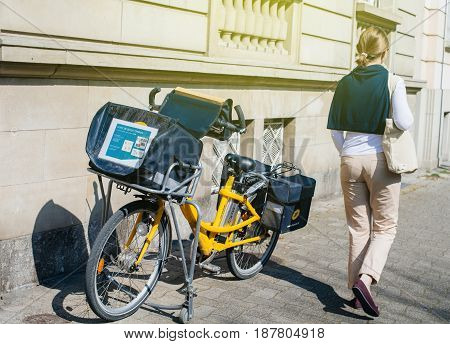 STRASBOURG FRANCE - APR 8 2017: Elegant French woman walking near Yellow La Poste postal bicycle parked ona wall in French city - postman went to deliver the mail