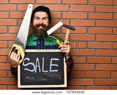 bearded man long beard brutal caucasian hipster with moustache holding various building tools: saw hammer roller paint board with inscription sale with happy smiling face on brick wall background