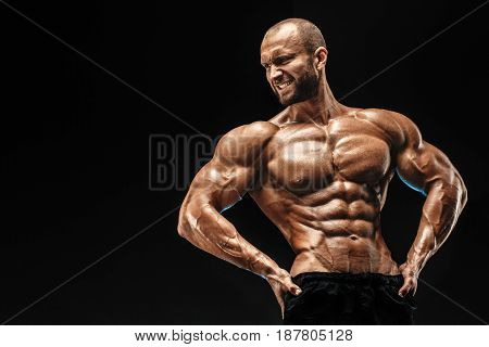 Strong bald bodybuilder with six pack. Strong bodybuilder man with perfect abs, shoulders, biceps, triceps and chest, personal fitness trainer flexing his muscles poster