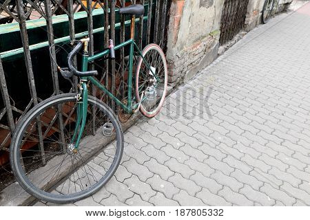 Old rusty cycling bike pinned to the fence