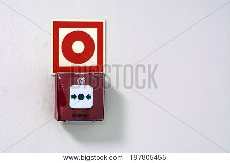 button fire alarm on a white wall in the supermarket