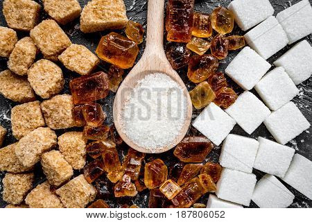 cooking sweets set with sugar in spoons on kitchen dark table background top view pattern