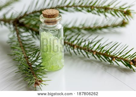 cosmetic spruce salt in bottles with fur branches for aromatherapy on white table background