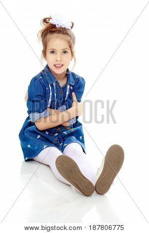The little blonde girl with a large white bow on the head and short denim dress.She sits on the floor turned sideways to the camera and stretching out his legs.Isolated on white background.