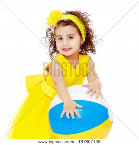 Funny curly baby girl in a bright yellow dress and bow on her head playing with a ball.Isolated on white background.