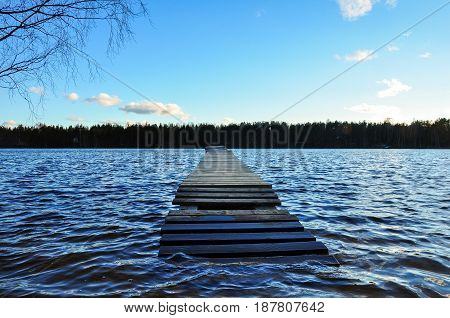 Flooded Wooden Bridge In The Blue, Waving Lake Water. Perspective View.