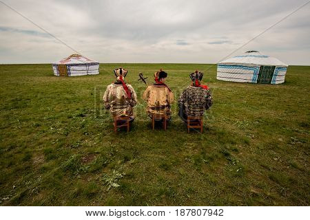 Three Kalmyk musicians in national costumes in the steppe against the background of yurts, the spring steppe. Russia