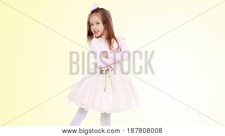 Dressy little girl long blonde hair, beautiful pink dress and a rose in her hair.One folded his arms.On a yellow gradient background.